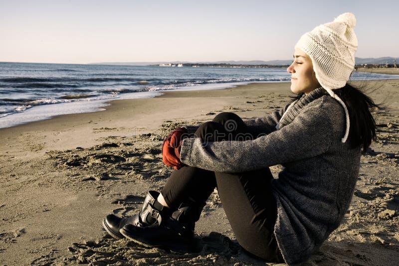 Glückliches schönes Mädchen, das Strand im Winter mit Hut genießt lizenzfreies stockbild