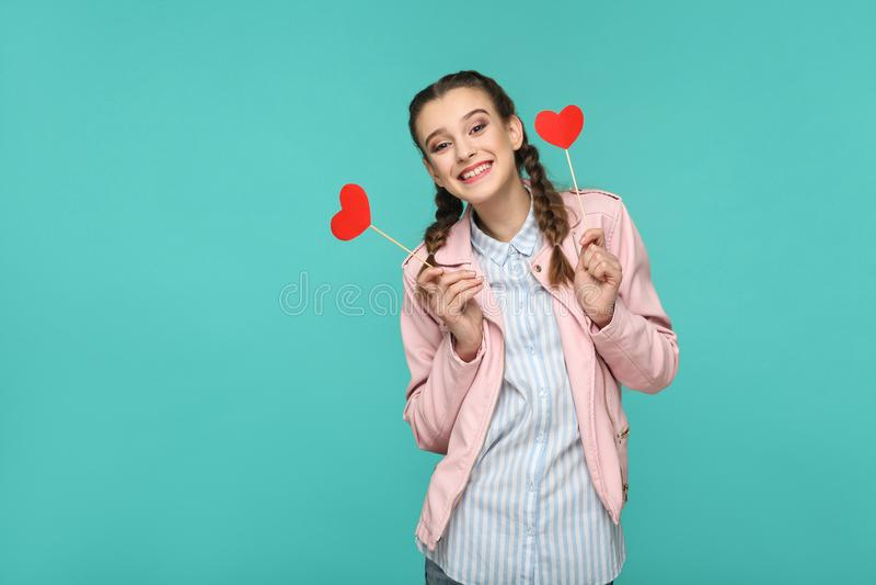 Glückliches schönes Mädchen in der zufälligen Art, in der Zopffrisur und im Rosa lizenzfreie stockfotografie