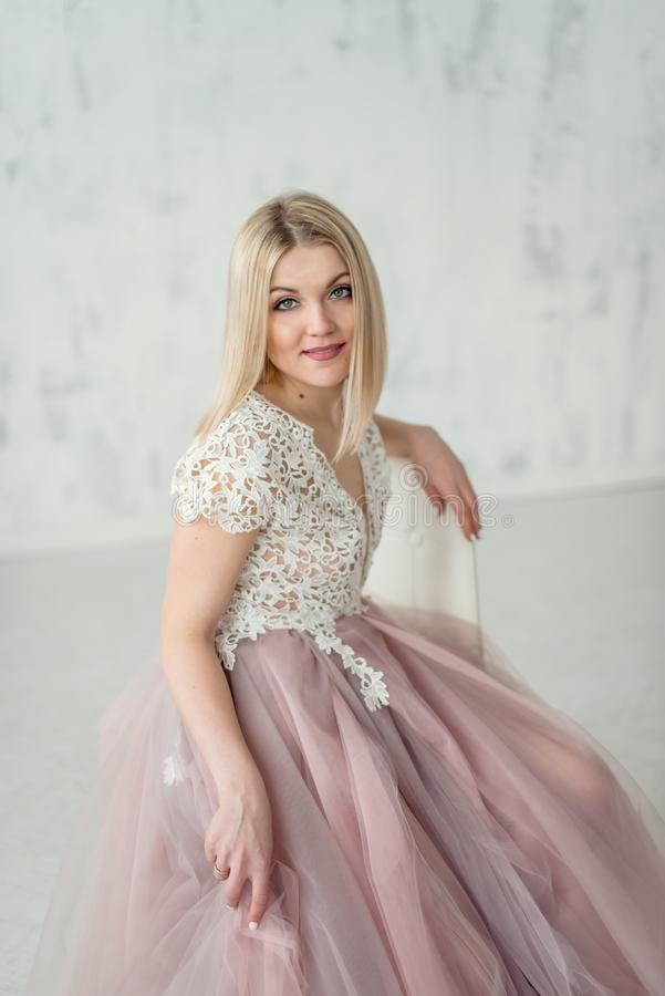 Glückliches schönes Mädchen in einem Abendkleid mit Spitze und rosa fartine auf dem Hintergrund einer weißen strukturellen Wand lizenzfreies stockbild