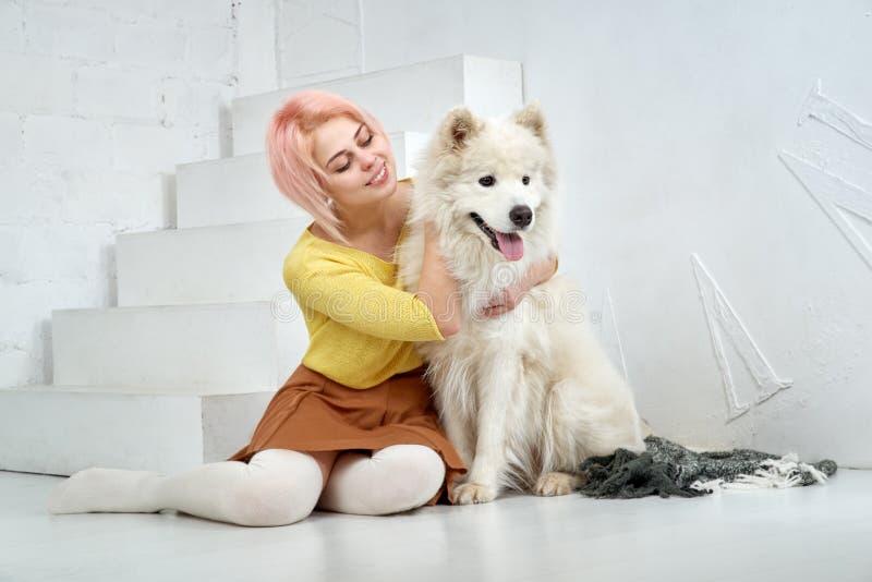 Glückliches schönes Mädchen und ihr großer weißer Hund, die mit Vergnügen an den Armen sitzt Eine schöne junge Frau und ihr Haust stockfoto