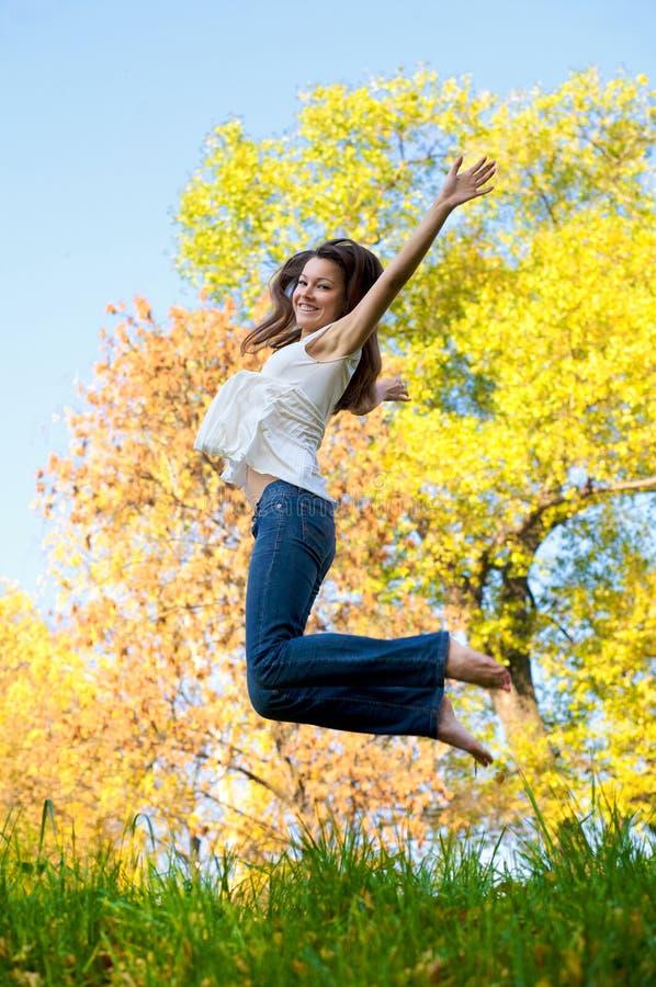 Glückliches schönes Mädchenspringen lizenzfreies stockbild