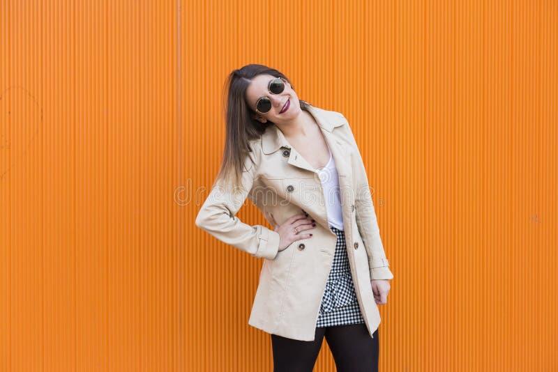 Glückliches schönes Tanzen der jungen Frau der Mode, das über Orange lächelt stockfotografie