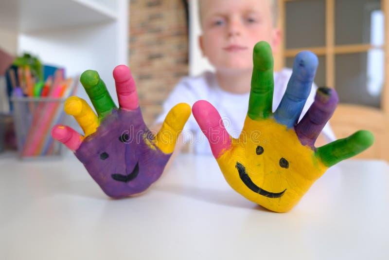 Glückliches schauendes Kind, das mit Farben in seinen Fingern, Nahaufnahmefoto spielt lizenzfreies stockbild