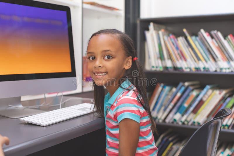 Glückliches Schulmädchen, das im Computerraum sitzt lizenzfreies stockbild