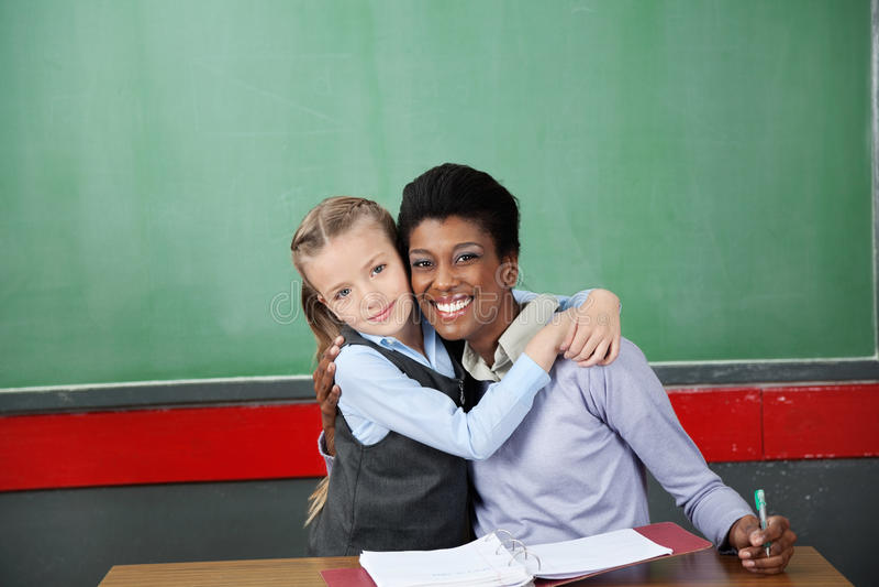 Glückliches Schulmädchen, das Lehrer At Desk umarmt stockbild
