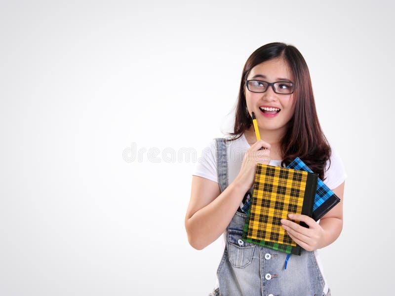 Glückliches Schulmädchen, das oben schaut, um Raum auf Weiß zu kopieren lizenzfreie stockfotografie