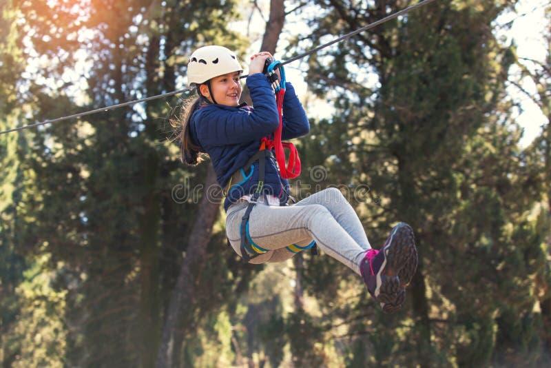 Glückliches Schulmädchen, das Tätigkeit in einem kletternden Erlebnispark genießt stockfotos