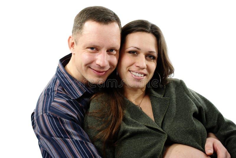 Glückliches schwangeres Paarumarmen stockfotos