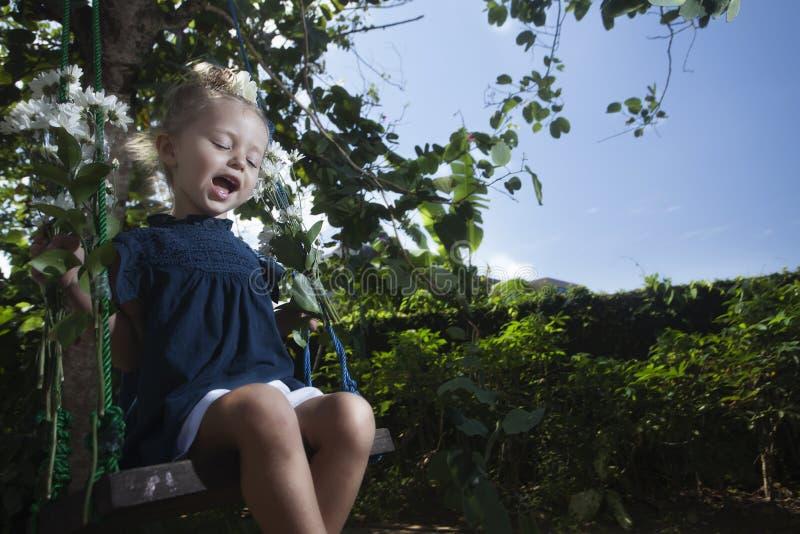 Glückliches Schwingen des kleinen Mädchens auf Kind-` s Tag- oder Mutter ` s Tag lizenzfreies stockfoto