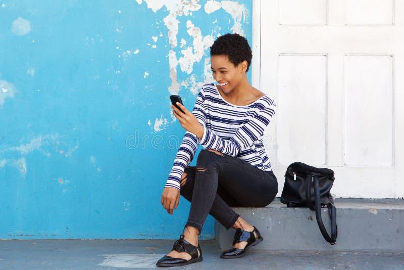 Glückliches Sitzen der jungen Frau äußer und Betrachten des Handys lizenzfreie stockfotografie