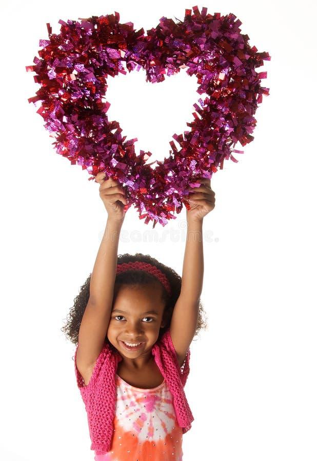 Glückliches spielerisches Kind, das Herz hält lizenzfreie stockfotografie