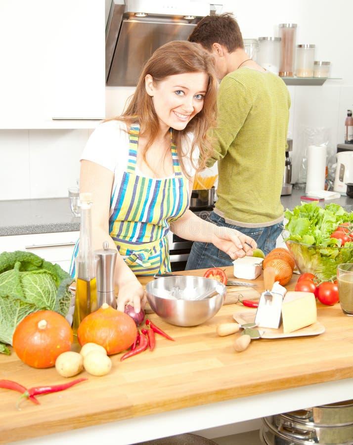 Glückliches sportliches Paar bereitet gesunde Nahrung auf heller Küche zu stockfotografie