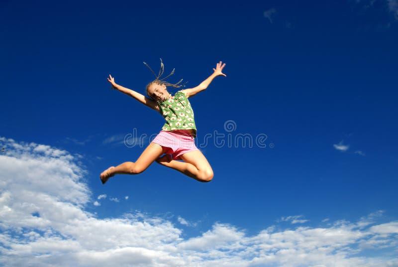 Glückliches springendes Mädchen und Himmel stockfotografie