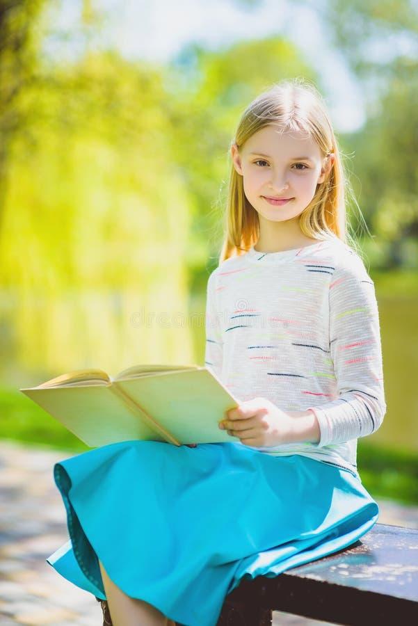 Glückliches stilvolles kleines Mädchen, das Buch im Freien halten lächelt stockfoto
