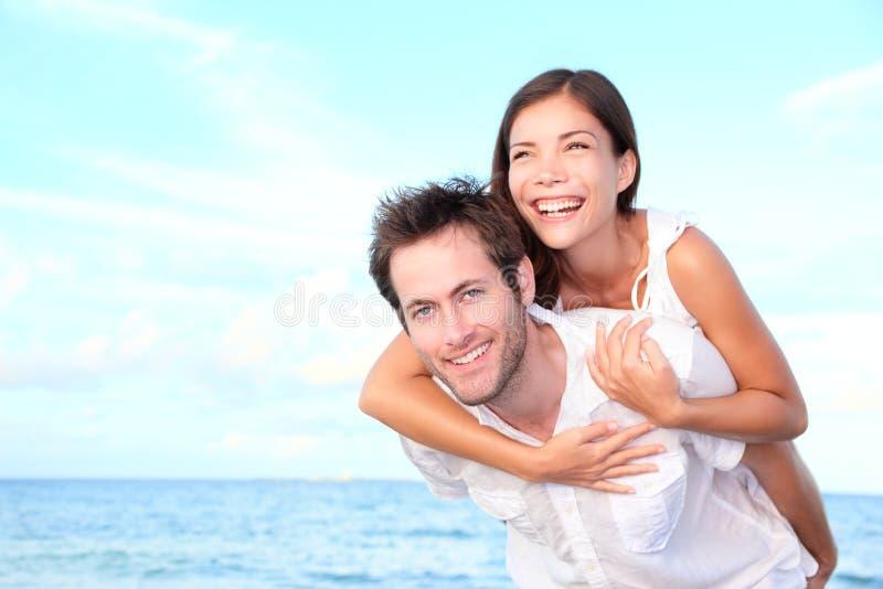 Glückliches Strandpaardoppelpol lizenzfreie stockfotos