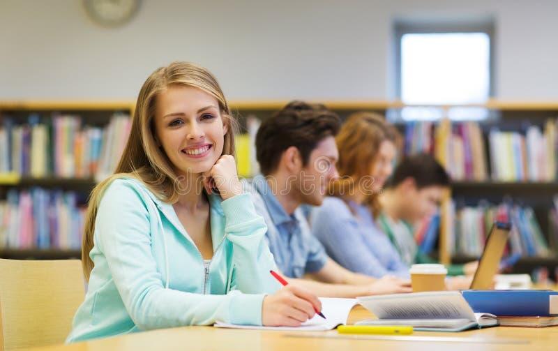 Glückliches Studentenmädchen, das zum Notizbuch in Bibliothek schreibt lizenzfreie stockfotografie