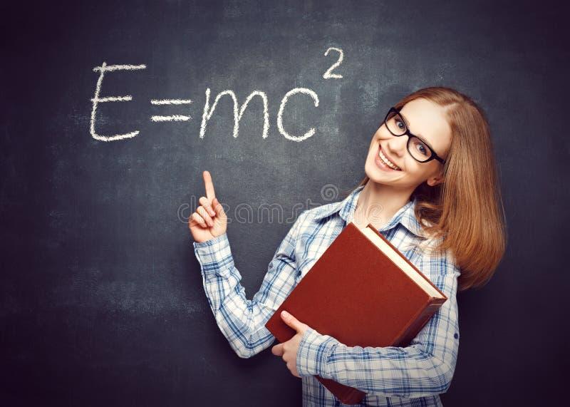 Glückliches Studentenmädchen mit Buch und Gläsern hat auf blackbo geschrieben lizenzfreie stockbilder