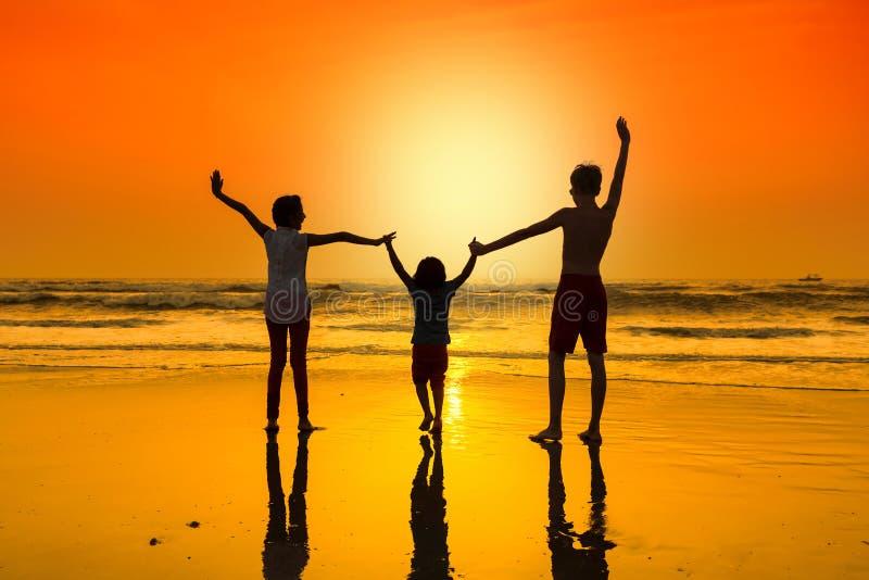 Glückliches Tanzen der jungen Leute am Strand auf Sonnenuntergang lizenzfreie stockfotografie