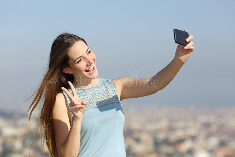 Glückliches tausendjähriges Mädchen, das draußen selfies nimmt lizenzfreie stockfotos