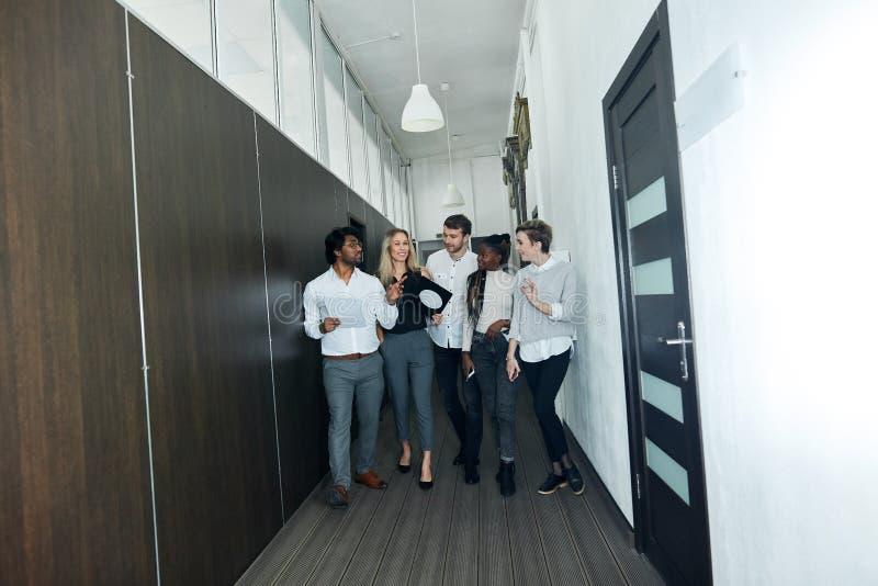 Glückliches Team von den Unternehmensfachleuten, die zuhause gehen und sprechen lizenzfreie stockbilder
