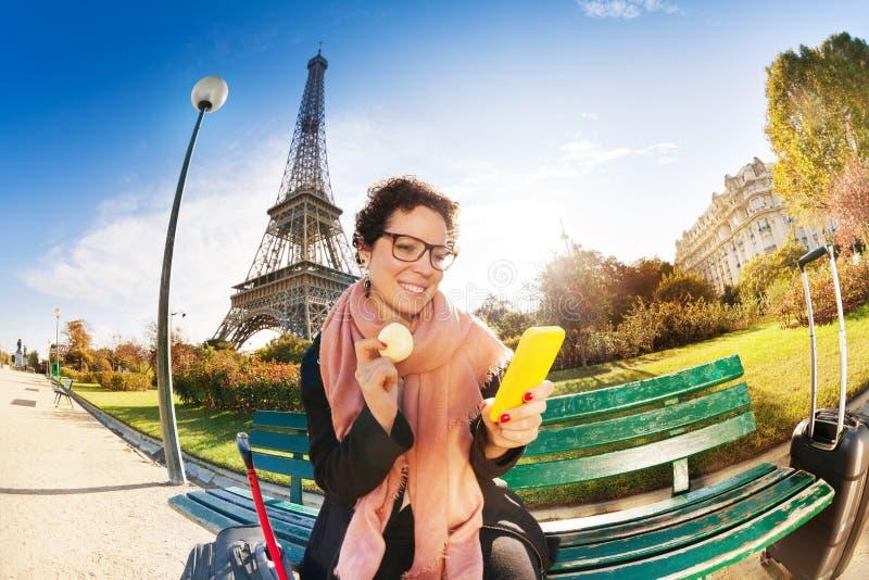 Glückliches touristisches Essen macaron nahe dem Eiffelturm lizenzfreie stockbilder