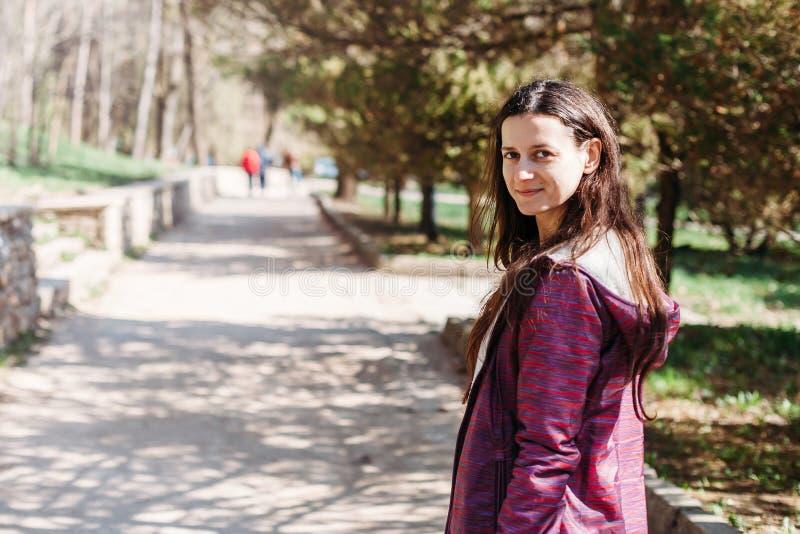 Glückliches touristisches Lächeln der jungen Frau, das in Park geht lizenzfreies stockfoto