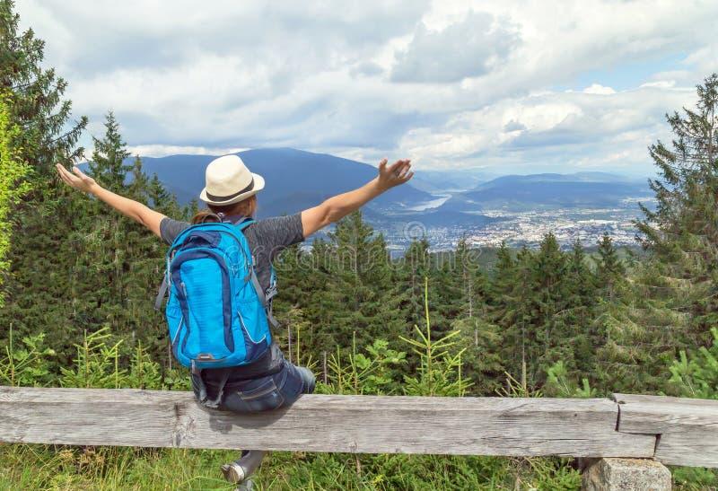 Glückliches touristisches Mädchen mit dem Anheben von den Händen und von Rucksack, die im österreichischen Alpenberg sitzen und S stockbilder
