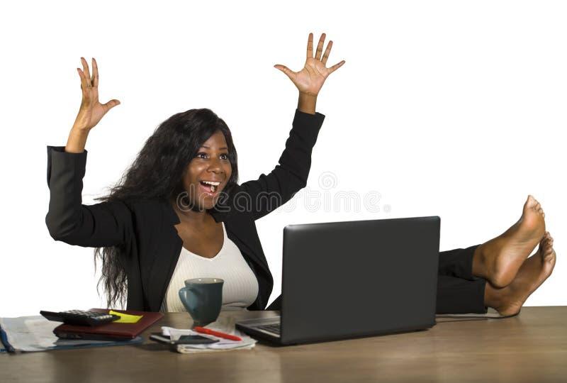 Glückliches und attraktives schwarzes afroes-amerikanisch Geschäftsfrauarbeiten aufgeregt mit Füßen auf dem Computertischlächeln  stockfotos