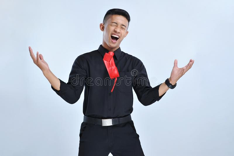 Glückliches und aufgeregtes Feiern des jungen asiatischen Geschäftsmannes, großen Erfolg ausdrückend und schreien das Feiern, gew lizenzfreie stockbilder