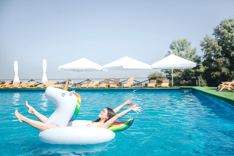 Glückliches und erfülltes Mädchen liegt auf Luftmatraze mitten in Swimmingpool Sie hält Hände und Beine in einer Luft Mädchen stockfoto