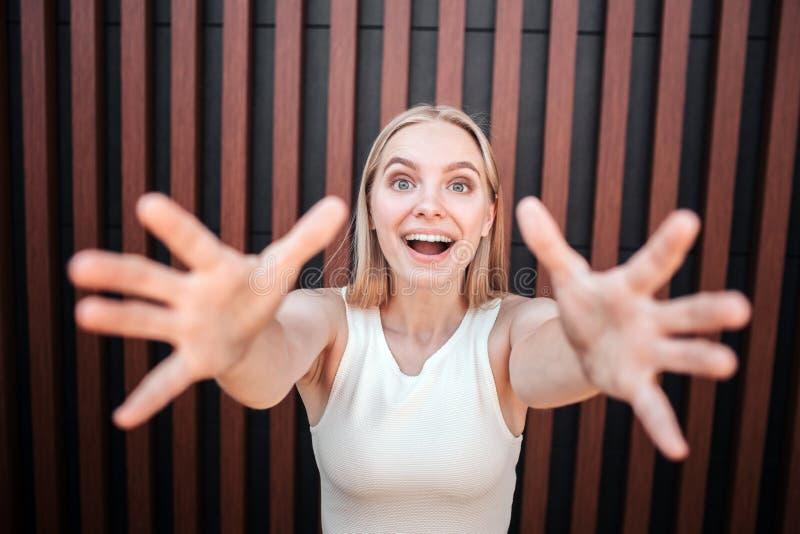 Glückliches und frohes Mädchen schaut auf Kamera und versucht, sie mit ihren Fingern zu erreichen Sie hält Augen breit sich öffne stockfotografie