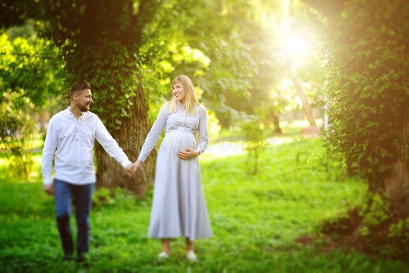Glückliches und junges schwangeres Paargehen im Freien lizenzfreie stockfotografie