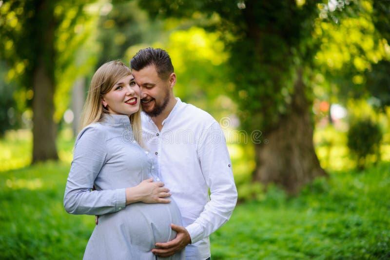 Glückliches und junges schwangeres Paarumarmen im Freien lizenzfreies stockbild