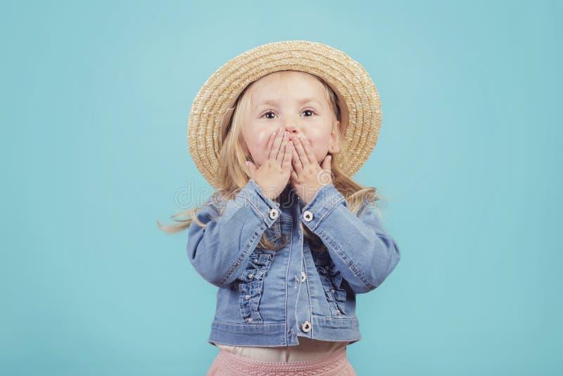 Glückliches und lächelndes Baby mit Hut auf blauem Hintergrund lizenzfreie stockbilder