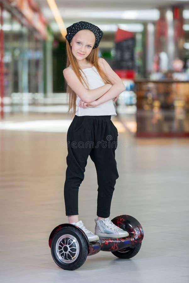 Glückliches und lächelndes Mädchen fährt auf minisegway an Handelsmall Jugendlichreiten auf Schwebeflug Brett oder gyroscooter lizenzfreies stockbild