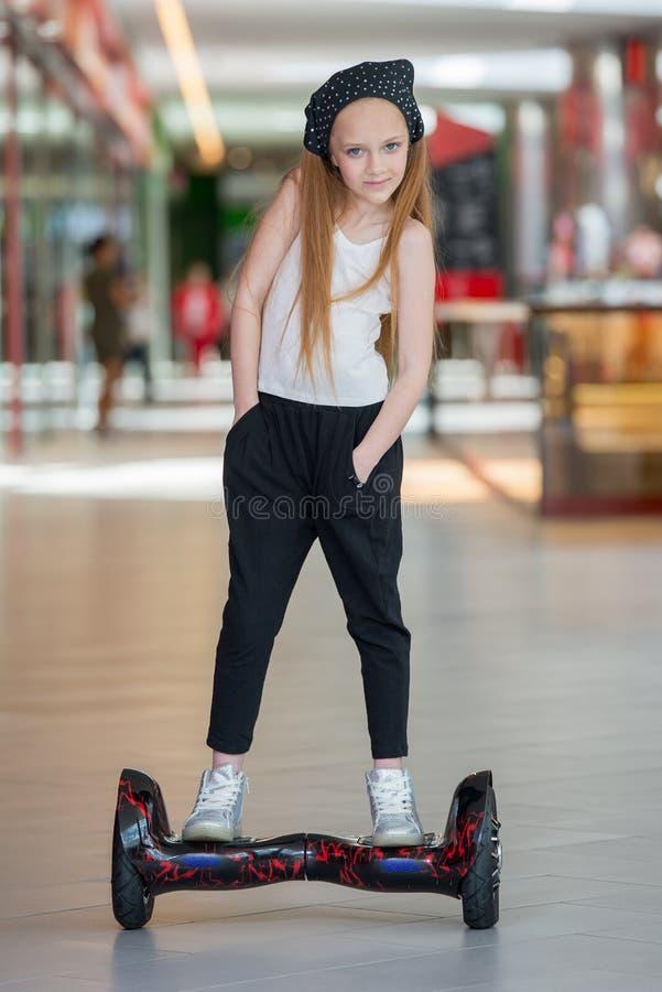 Glückliches und lächelndes Mädchen fährt auf minisegway an Handelsmall Jugendlichreiten auf Schwebeflug Brett oder gyroscooter stockfotos