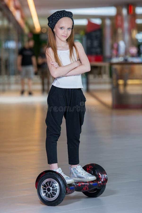 Glückliches und lächelndes Mädchen fährt auf minisegway an Handelsmall Jugendlichreiten auf Schwebeflug Brett oder gyroscooter stockfoto