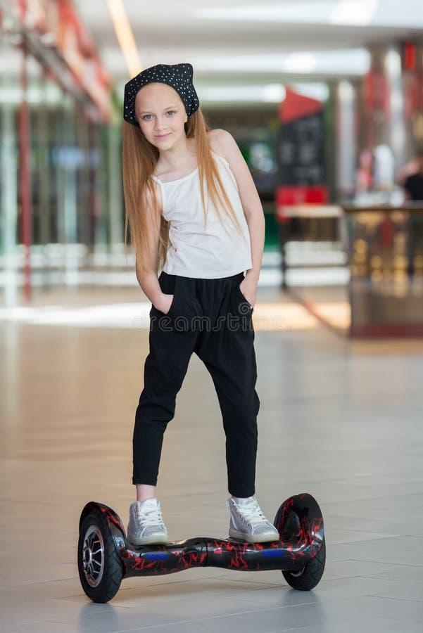 Glückliches und lächelndes Mädchen fährt auf minisegway an Handelsmall Jugendlichreiten auf Schwebeflug Brett oder gyroscooter stockbild
