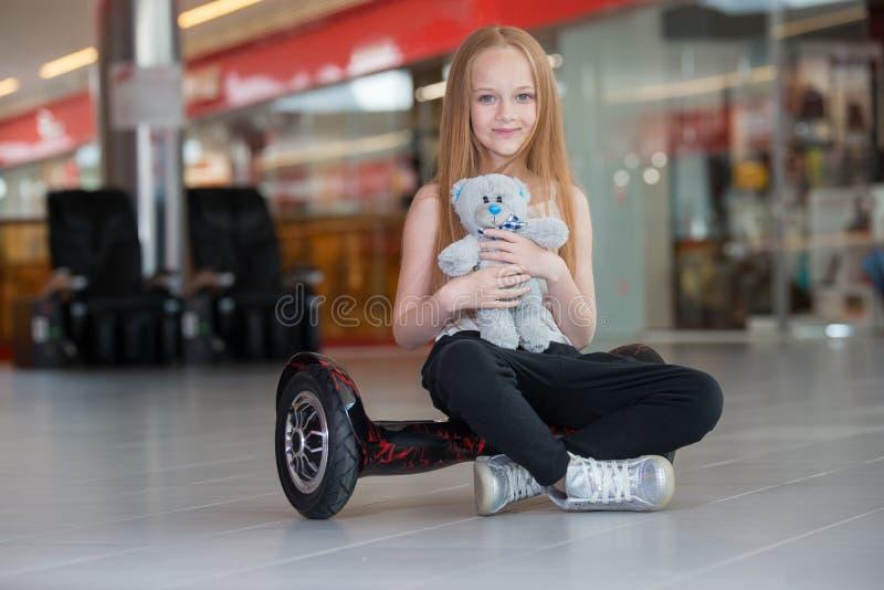 Glückliches und lächelndes Mädchen mit mini segway und Plüschbärnpuppe an Handelsmall Jugendlichreiten auf Schwebeflug Brett oder stockfotos
