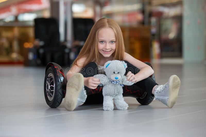 Glückliches und lächelndes Mädchen mit mini segway und Plüschbärnpuppe an Handelsmall Jugendlichreiten auf Schwebeflug Brett oder lizenzfreie stockfotografie