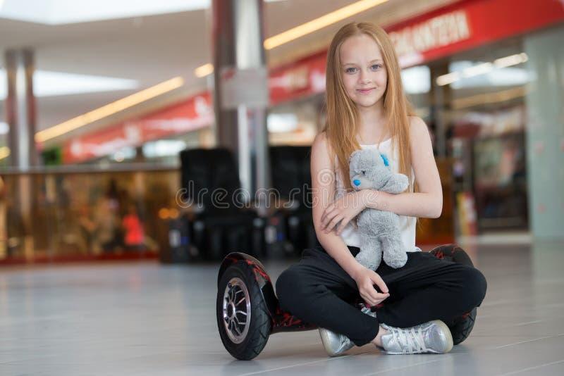 Glückliches und lächelndes Mädchen mit mini segway und Plüschbärnpuppe an Handelsmall Jugendlichreiten auf Schwebeflug Brett oder lizenzfreie stockbilder