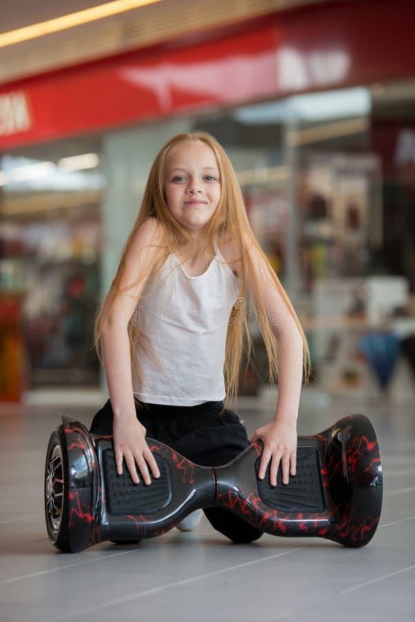 Glückliches und lächelndes Mädchen mit minisegway an Handelsmall Jugendlichreiten auf Schwebeflug Brett oder gyroscooter lizenzfreie stockfotografie
