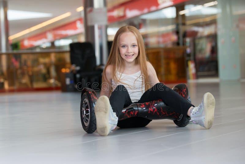 Glückliches und lächelndes Mädchen mit minisegway an Handelsmall Jugendlichreiten auf Schwebeflug Brett oder gyroscooter stockfoto