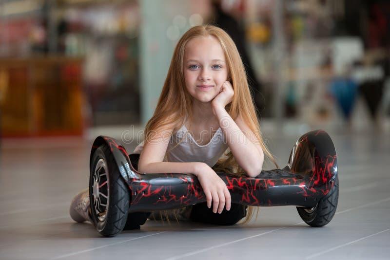 Glückliches und lächelndes Mädchen mit minisegway an Handelsmall Jugendlichreiten auf Schwebeflug Brett oder gyroscooter stockfotos
