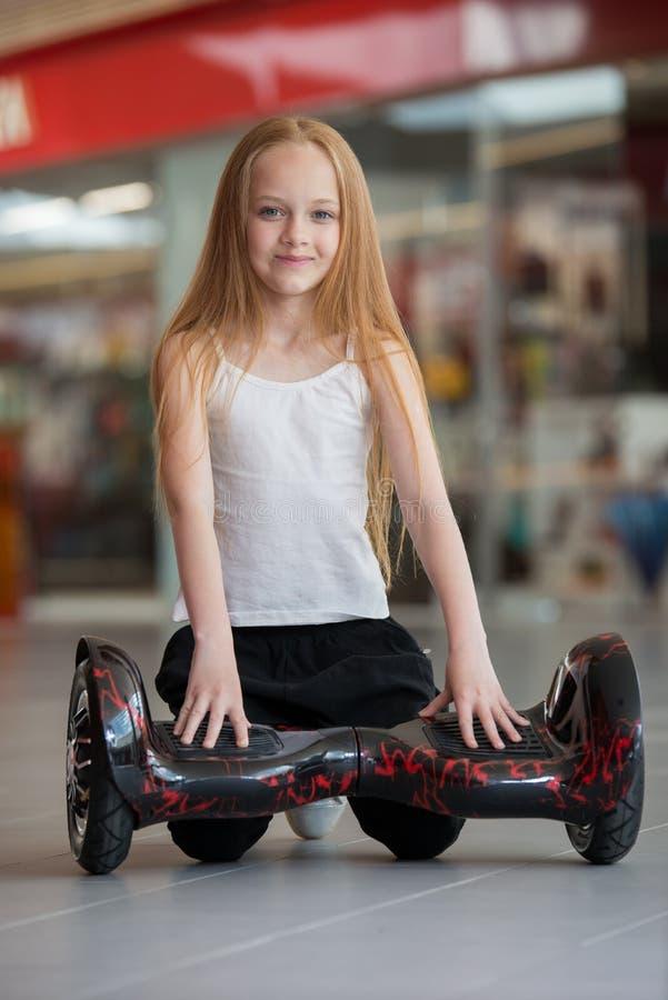 Glückliches und lächelndes Mädchen mit minisegway an Handelsmall Jugendlichreiten auf Schwebeflug Brett oder gyroscooter stockbilder