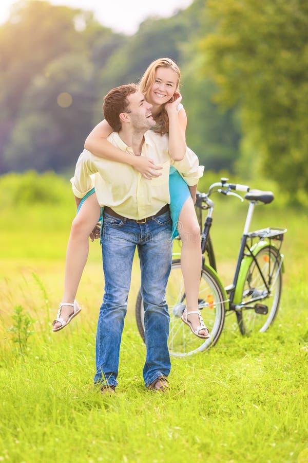 Glückliches und nettes junges Paar-Doppelpol, das Spaß draußen hat lizenzfreie stockbilder