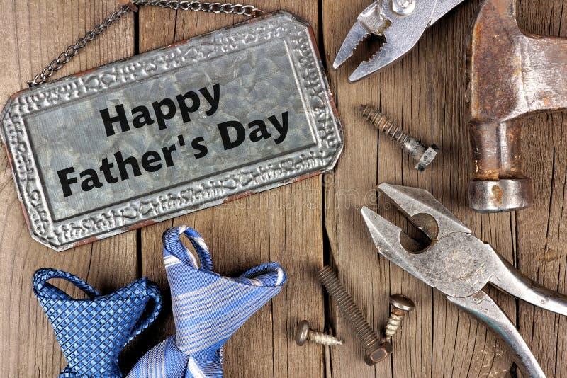 Glückliches Vatertagsmetallschild mit Werkzeugen und Bindungen auf Holz stockfotografie