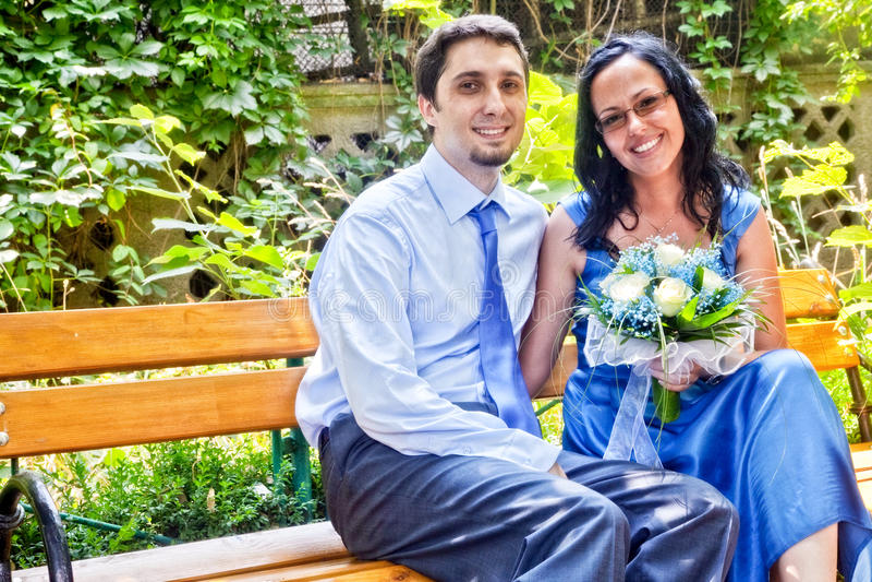 Glückliches verheiratetes Paar, das auf Bank sitzt stockfotografie