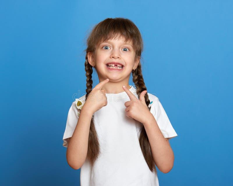 Glückliches verlorenes Zahnmädchenporträt, Studiotrieb auf blauem Hintergrund lizenzfreie stockfotos