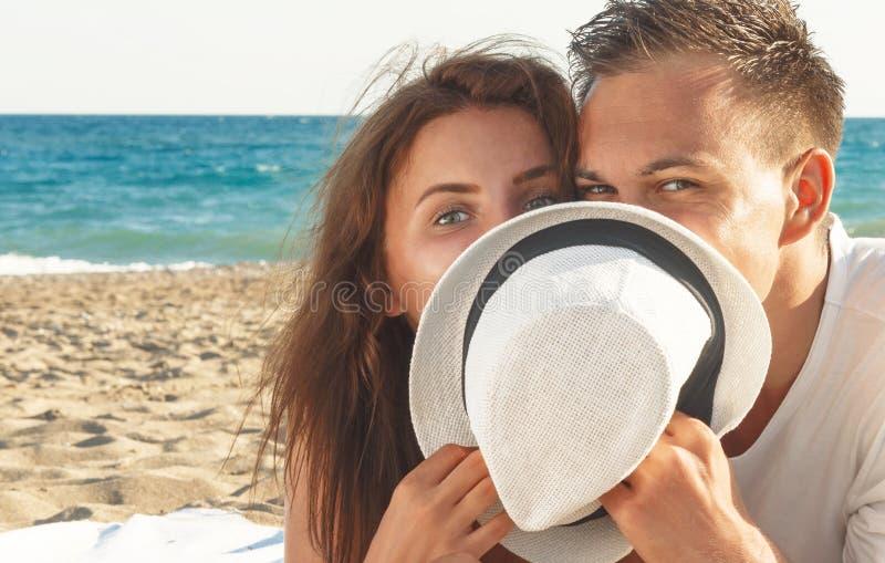 Glückliches Verstecken der jungen Paare hinter Hut lizenzfreie stockbilder